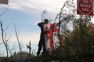 Warrior raises Mi'kmaq flag at blockade. Photo: Miles Howe